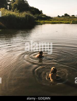 Boy and girl swimming in river