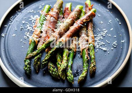 Asperges grillées enveloppé dans du jambon de Parme avec du parmesan, sauge et thym Banque D'Images