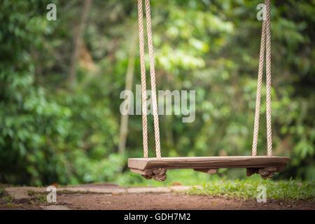 Fermer l'accent sur swing assise en bois suspendu par corde en vertu de l'arbre qui flotte au-dessus du sol marbre Banque D'Images