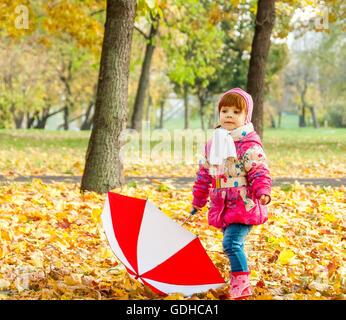 Une petite fille qui marche dans le parc avec un parapluie Banque D'Images
