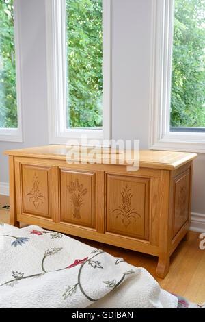 Chêne sculpté coffre de cèdre avec des arbres à travers les fenêtres et une couverture dans la chambre Banque D'Images
