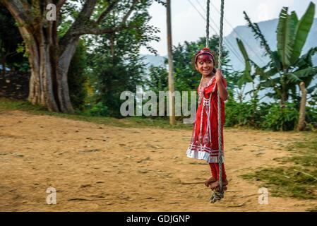 Girl in red dress népalais joue sur une balançoire bambou traditionnel appelé linge ping. Banque D'Images