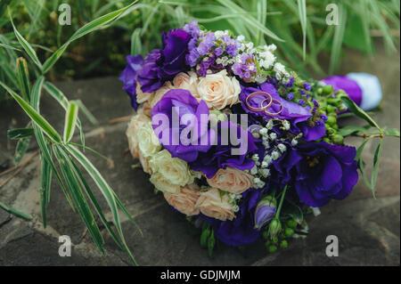 Bouquet de mariage. anneaux d'or et deux verres de shampagne sur l'arrière-plan d'herbe verte et la pierre. Banque D'Images