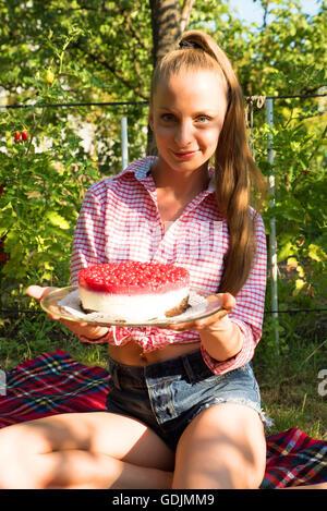 Une jeune femme ayant un pique-nique avec un gâteau dans le jardin. Banque D'Images