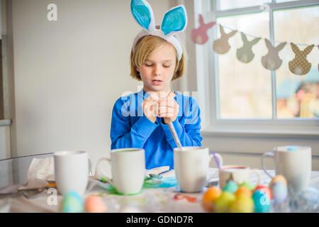 Garçon à la table portant des oreilles de lapin décorer les œufs de Pâques Banque D'Images