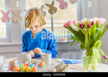 Garçon à la table décorer les œufs de Pâques Banque D'Images