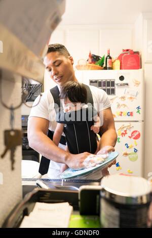Père avec bébé en transporteur, lave-vaisselle Banque D'Images