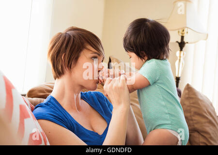 Mother sitting on sofa kissing baby's hands Banque D'Images