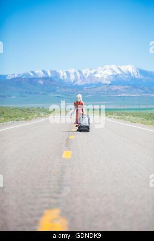 Vue arrière de style années 1950 jeune femme marcher seule sur l'autoroute 50 tirant valise à roulettes, Nevada, USA Banque D'Images