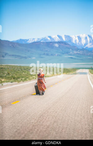 Jeune femme style années 50 marcher seule sur l'autoroute 50 tirant valise à roulettes, Nevada, USA Banque D'Images