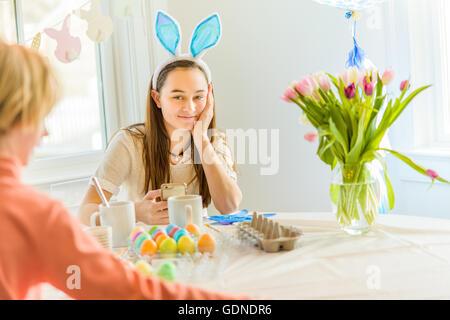 Adolescente et son frère à table la teinture des œufs durs pour Pâques Banque D'Images