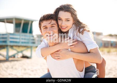 Portrait of young man piggybacking sa petite amie sur la plage Banque D'Images