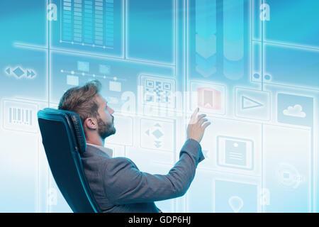 Homme assis dans une chaise, à l'aide d'écran graphique, touching screen Banque D'Images