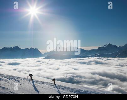 Deux alpinistes sur une pente enneigée au-dessus d'une mer de brume dans une vallée alpine, Alpes, Canton du Valais, Banque D'Images