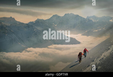 Deux alpinistes sur une pente enneigée sur une mer de brume dans une vallée alpine, Alpes, Canton du Valais, Suisse Banque D'Images