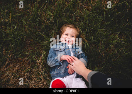 Young Girl lying on grass, chatouillement par sa mère, overhead view Banque D'Images