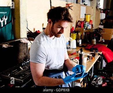 Homme mécanicien dans l'atelier, l'analyse des données de l'ordinateur du véhicule, à l'aide de mobile phone Banque D'Images