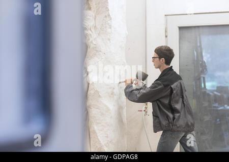 Tailleur de pierre à l'aide d'un burin et d'un maillet pour créer la sculpture Banque D'Images