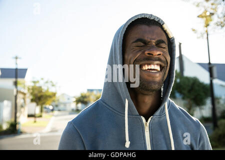 Portrait of man wearing hooded top les yeux fermés riant Banque D'Images