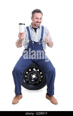 Mécanicien en salopette bleue beau faire comme geste et de boire un café chaud isolé sur fond blanc Banque D'Images