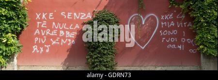 ,Graffiti pulvérisé sur une pierre, brique, mur, avec des lettres italiennes, sur la maçonnerie avec du texte blanc, Banque D'Images