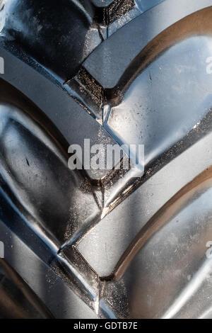 Close up d'un grand un grand noir, le pneu du tracteur avec de grands escaliers. Banque D'Images