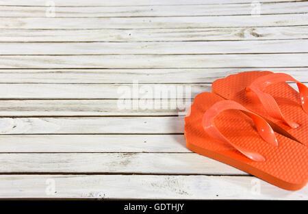 L'orange vif des tongs sur bois blanchis. Banque D'Images
