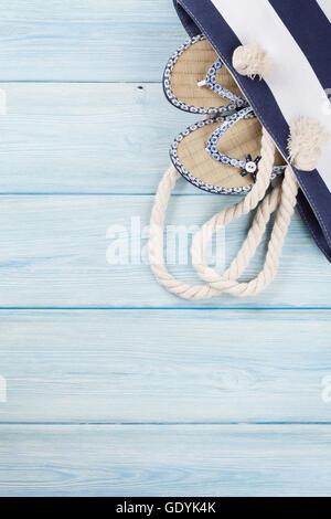 Accessoires de plage. Sac avec des tongs sur fond de bois. Top View with copy space Banque D'Images