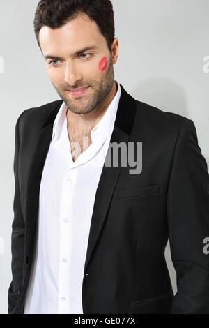 Young caucasian businessman with lipstick kiss marque sur sa joue. Banque D'Images