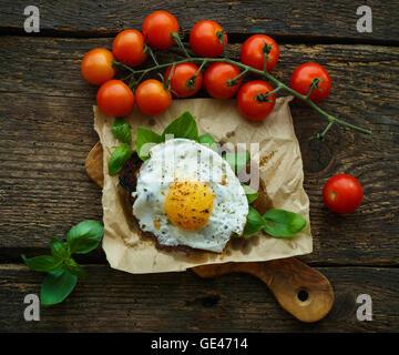 Oeufs brouillés sur du pain grillé au basilic, tomates cerise et d'épices sur un fond de bois Banque D'Images
