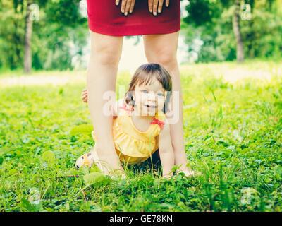 Bébé âgé d'un an entre la mère fille jambes à l'extérieur Banque D'Images