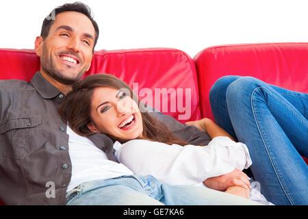 Cheerful young couple relaxing on sofa. Aimer les hommes et les femmes sont partenaires dans l'emploi temporaire. Banque D'Images