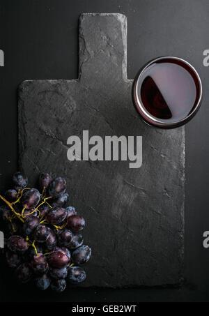 Verre de vin rouge et les raisins sur noir ardoise sur fond sombre Banque D'Images