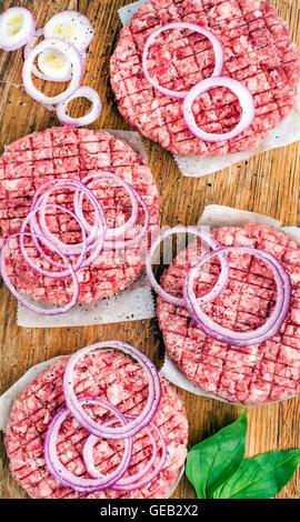 Escalope de viande de boeuf haché cru pour faire des hamburgers avec oignons et épices sur fond de bois Banque D'Images