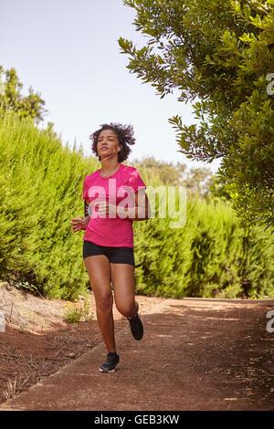 Une jeune coureuse dehors pour un jogging sur un sentier de gravier entouré par des bagues, de porter des vêtements Banque D'Images