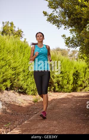 Une jeune femme jogger sortir courir sur un chemin de gravier avec des buissons derrière elle, vêtu de vêtements Banque D'Images