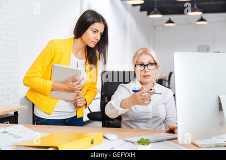 Deux jolies jeunes et matures femmes bureau ayant une réunion de remue-méninges à la table dans le bureau Banque D'Images