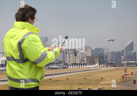 Un ingénieur de l'environnement surveille les niveaux de bruit à l'aéroport de London city en avion atterrit. canary Banque D'Images