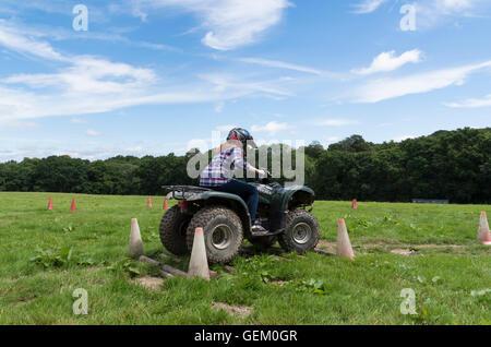 Redhaired girl à chemise équitation quad dans la campagne à travers les obstacles sur un voyage d'une journée de plein air.