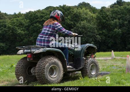 Redhaired girl à chemise équitation quad dans la campagne à travers les obstacles sur un voyage d'une journée de Banque D'Images