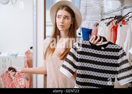 Jeune femme confuse réfléchi le choix entre deux robes en magasin de vêtements