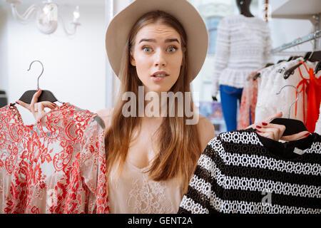 Jeune femme très confus le choix d'habiller dans une boutique de vêtements Banque D'Images