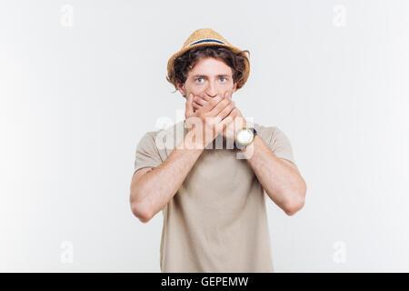 Beau jeune homme coveres à hat sa bouche par les mains sur fond blanc Banque D'Images