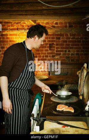 Un homme dans un tablier à rayures bleu et blanc, la cuisson du poisson sur une plaque chaude sur une cuisinière. Banque D'Images