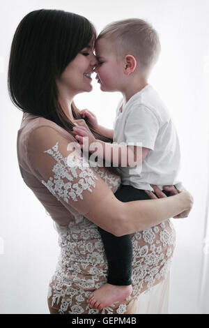 Une femme enceinte tenant son jeune fils dans ses bras.