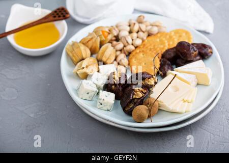 Assiette de fromage avec des craquelins, des dates et des écrous