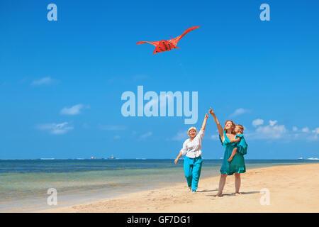 Relations sérieuses in a happy family on beach - grand-mère, mère et fille à pied le long d'ocean surf. Senior woman s'exécute avec le vol de cerf-volant rouge.