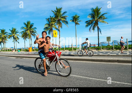 RIO DE JANEIRO - le 6 mars 2016: Deux jeunes Brésiliens de la bicyclette geste comme ils passent sur le bord de Banque D'Images
