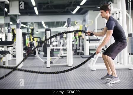 Jeune homme luttant avec l'exercice de corde au gymnase Banque D'Images