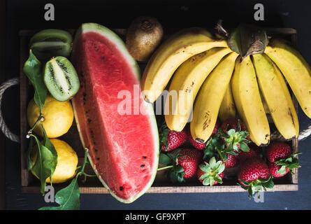Divers fruits tropicaux colorés en sélection plateau en bois sur fond sombre Banque D'Images